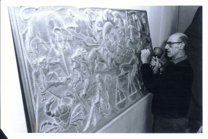 E. Mervyn Taylor works on a carved panel that he was commissioned for Broadcasting House, Wellington, in 1963. Entitled Time and space, it showed the sun and moon and all the signs of the zodiac carved in low relief on a kauri panel. Taylor often worked day and night to complete the commission. Image: E. Mervyn Taylor Estate
