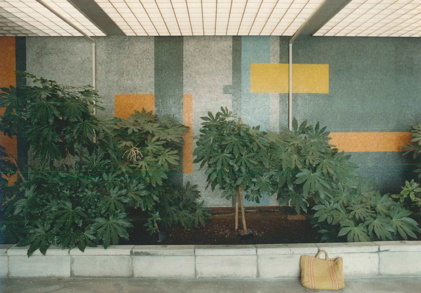 A geometric mosaic tile mural featuring bands and rectangles in greys, with orange and yellow accents, 1987